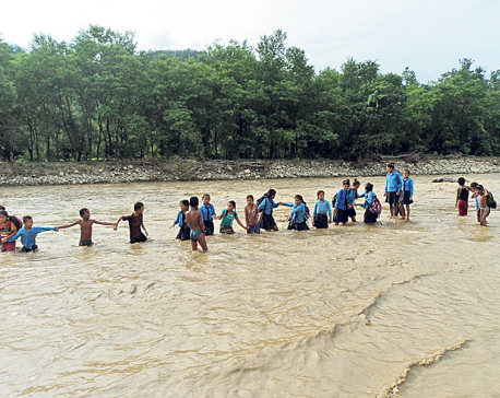 Children brave flooded river to reach school