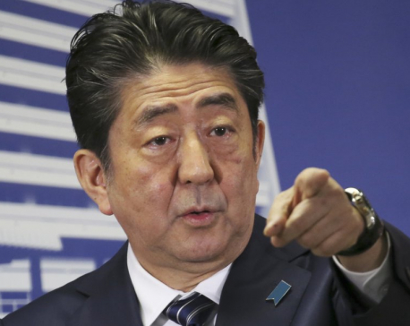 The Latest: Exit polls show Abe's ruling bloc wins elections