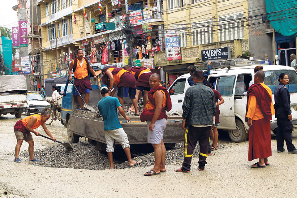 Monks take initiative to fill the potholes of Bauddha-Jorpati road