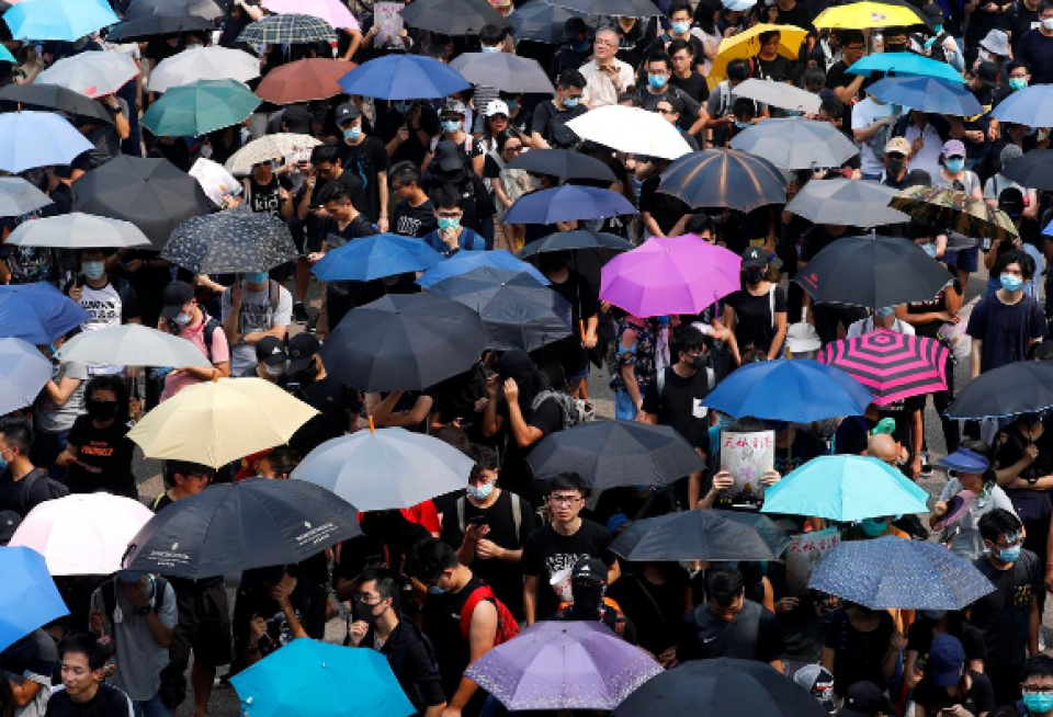 Thousands march in Hong Kong as police in black masks look on
