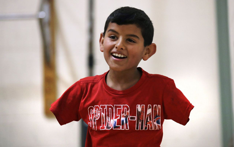 Armless Syrian boy thrives in US, hopes family can join him